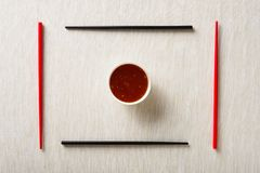 Chopsticks and bowl with sauce on table mat Royalty Free Stock Image