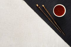 Chopsticks and bowl with sauce on table mat Royalty Free Stock Images
