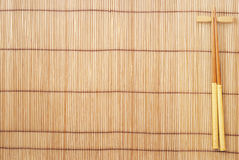 Chopsticks on brown bamboo matting background Stock Photos