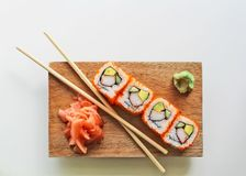 Chopsticks and sushi maki rolls on a wood plate - japanese food. Chopsticks with California sushi maki rolls, wasabi and ginger on a wood plate - japanese food royalty free stock photos