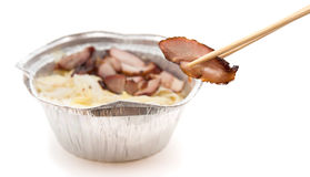 Chopsticks catching a piece of barbeque pork with a fast food bowl at background Stock Photography