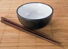 Chopsticks with  ceramic bowl on bamboo mat Royalty Free Stock Image