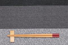 Chopsticks and chopsticks rest. On table background Stock Images