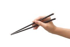 Chopsticks da terra arrendada da mão foto de stock