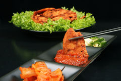 Chopsticks dipping Korean chicken barbeque in sauce Stock Photography