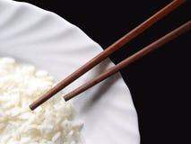 Chopsticks e uma placa com arroz Fotografia de Stock Royalty Free