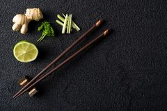 Chopsticks and food ingredients on black stone table Royalty Free Stock Photo