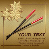 Chopsticks on a gold background with abstract flowers Stock Images