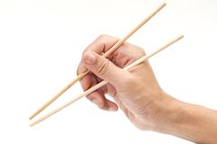 Chopsticks on hand. Isolated on white background stock images