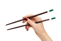 Chopsticks in a hand Stock Images