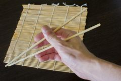 Chopsticks in hand in the background of a bamboo sushi mat royalty free stock photo
