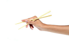Chopsticks in a hand. Chopsticks in a beautiful hand Royalty Free Stock Photography