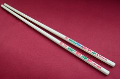 Chopsticks with hieroglyphics on the red background Royalty Free Stock Image