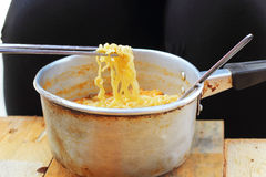 Chopsticks holding asian noodles in pot Royalty Free Stock Photos