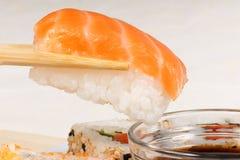 Chopsticks holding a piece of nigiri sushi Stock Photo