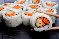 Chopsticks holding sushi in front of more sushi Royalty Free Stock Photos