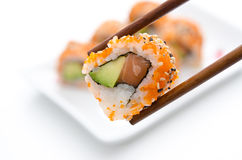 Chopsticks holding sushi roll Stock Photo