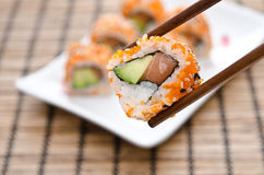 Chopsticks holding sushi roll Royalty Free Stock Images