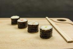 Chopsticks and hosomaki on a wooden board. Four hosomaki and chopsticks on a wooden board Stock Photos
