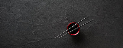 Chopsticks i puchar z soja kumberlandem na czarnym tle Fotografia Stock