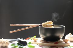 Chopsticks of instant noodles in cup with smoke rising and garli royalty free stock image