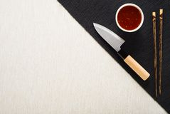 Chopsticks, knife and bowl with sauce on table mat Stock Photography