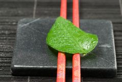 Chopsticks and leaf Stock Images