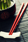 Chopsticks and a lucky bamboo plant Royalty Free Stock Photo
