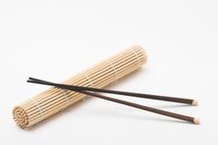 Chopsticks and makisu. Chopsticks and rolled maki sushi bamboo makisu royalty free stock photography