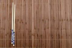 Chopsticks on the mat Stock Photos
