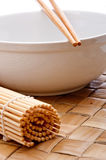 Chopsticks On A White Bowl With A Sushi Mat Stock Photography