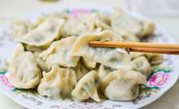 Chopsticks Pick Up Boilded Chineses Dumplings From A Plate. Royalty Free Stock Photos