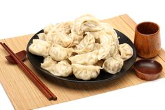 Chopsticks Pick Up Boilded Chineses Dumplings from a Plate. The Dumpling, called Jiaozi in Chinese, is a popular traditional Chine. Se food, especially during stock images