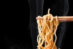 Chopsticks pick up tasty noodles with smoke on dark background. Noodles stock images