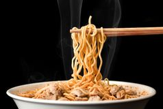 Chopsticks pick up tasty noodles with smoke on dark background. Ramen in white bowl. Noodle royalty free stock images