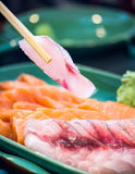 Chopsticks picking a pink sashimi from plate Royalty Free Stock Photo
