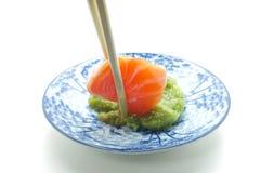 Chopsticks pinch fresh salmon sushi and wasabi Royalty Free Stock Image