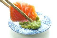 Chopsticks pinch fresh salmon sushi and wasabi Stock Photo