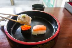 Chopsticks are pinch long tail tuna sushi. Japanese food style. Stock Image