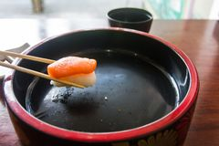 Chopsticks are pinch salmon sushi. Japanese food style. Royalty Free Stock Images