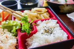 Chopsticks are pinch seaweed on bento set. Japanese food style. Stock Photo