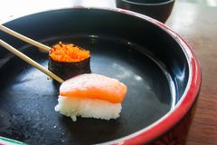 Chopsticks are pinch shrimp eggs sushi. Japanese food style. Royalty Free Stock Images