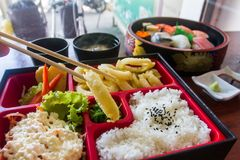 Chopsticks are pinch squid fried in bento set. Japanese food style. Stock Photography