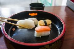 Chopsticks are pinch squid sushi. Japanese food style. Stock Photo