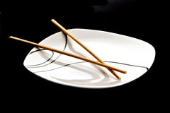 Chopsticks and plate. Wood chopsticks and asian style plate against black background Stock Photos
