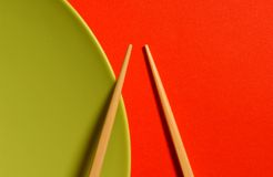 Chopsticks with plate. Chopsticks with green plate and red table Stock Photography