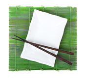 Chopsticks and plate over bamboo mat Royalty Free Stock Photo