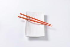 Chopsticks on plate Royalty Free Stock Image