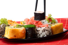 Chopsticks pull out a roll of a sushi. From a plate on a white background Royalty Free Stock Photos