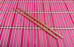 Chopsticks on red bamboo matting background Royalty Free Stock Photography